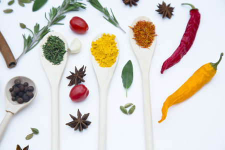 Cooking Hot Spicy Food Concept. Dry spices and herbs in wooden spoons, fresh herbs, cherry tomatoes and chili peppers, white background, top view, mock up