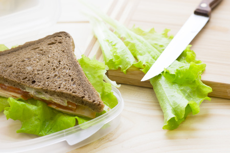Healthy Lunch Concept. Rye bread sandwich with vegetables in a box, cutting board and knife light wooden background, close up