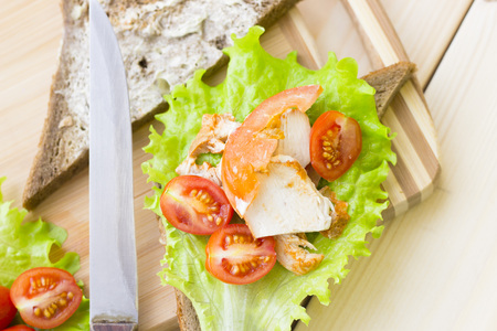 Healthy Lunch Concept. Preparing rye bread sandwich with chicken, lettuce and cherry tomatoes, light wooden background, top view