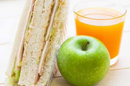 Healthy Lunch Concept. Wheat bread sandwich with ham and cheese,apple and a glass of juice, close up