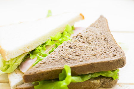 Healthy Lunch Concept. Wheat bread and rye bread sandwiches with ham and cheese, light wooden background, close up