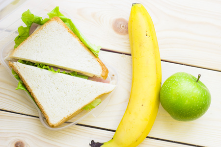 Healthy Lunch Concept. Wheat bread sandwiches with ham and cheese, apple and banana, light wooden background, top view Stock Photo