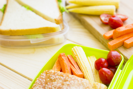 Healthy Lunch Concept. Lunch box food assortment: sandwiches, baby corns, cherry tomatoes, carrots, fruit, light wooden background, top view