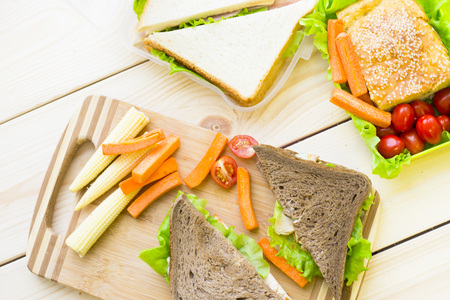 Healthy Lunch Concept. Lunch box food assortment: rye and wheat bread sandwich and vegetables, light wooden background, top view Stock Photo