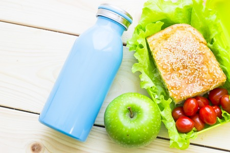 Healthy Lunch Concept. Pie with seasam, cherry tomatoes and lettuce in a lunch box, apple and a blue bottle, light wooden background, top view