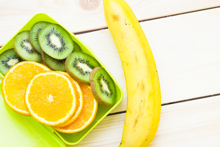 Healthy Lunch Concept. A green lunch box with sliced orange and kiwi and banana, light wooden background, close up, top view