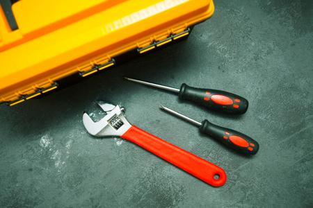 Repair modern tools: yellow box on dark stone background, top view, copy space Standard-Bild