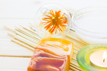 Spa and wellness setting with yellow flower, green candle, oil, cinnamon and soap on wooden white background closeup