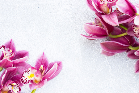 Spa and wellness setting with orchid flower, oil on wooden white background closeup