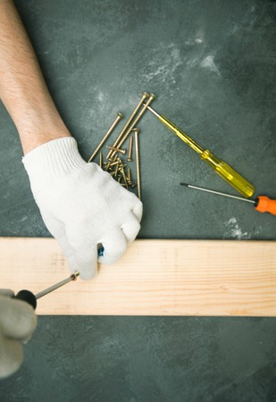 Repair modern tools: man hands in gloves on dark stone background, top view, copy space