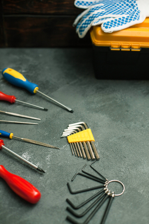 Repair modern tools: screwdriver and gloves on dark stone background, top view, copy space