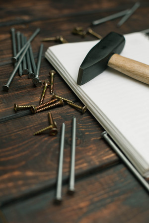 Repair modern tools: notepad and hummer on dark wooden background, top view, copy space