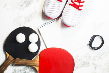 Sport fitness, weight loss concept.  racket, balls, notepad, sneakers on white wooden background. Vintage retro  filter Stock fotó