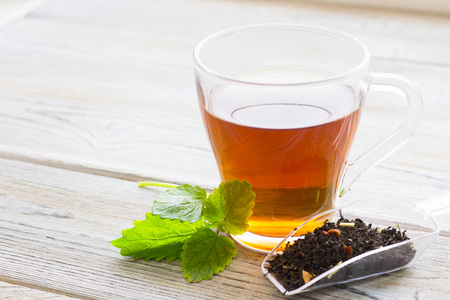 Black tea ceremony - glass full of tea, tea leaves, spices on a wooden boards background. Top view