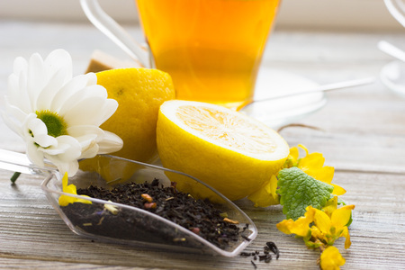 Black tea ceremony - glass full of tea, tea leaves, sugar, yellow lemon, spices on a wooden boards background. Top view