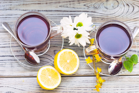 Black tea ceremony - glass full of tea, glass pot, tea leaves, sugar, yellow lemon, flower, spices on a wooden boards background. Top view