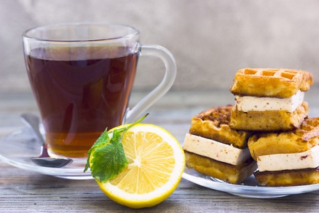 Black tea ceremony - waffles, glass full of tea, glass pot, tea leaves, sugar, yellow lemon, flower, spices on a wooden boards background. Top view