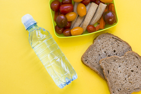 School lunch box. Bread, a bottle of water, candies, baby corns, carrot and tomatoes in green plastic container. Top view, yellow background
