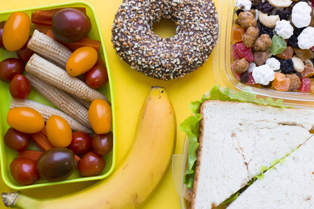 School lunch box. Sandwich, a banana, candies, baby corns, carrot and tomatoes in green plastic container. Top view, yellow background Stock Photo