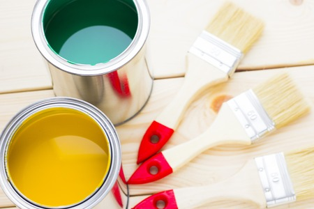 House renovation concept, colorfull paint cans and paintbrushes on wooden background top view Standard-Bild - 115543514