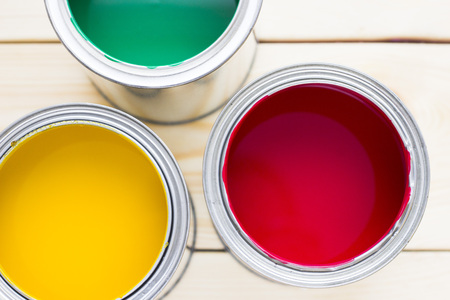 House renovation concept, colorfull paint cans on wooden background top view Standard-Bild - 115543515