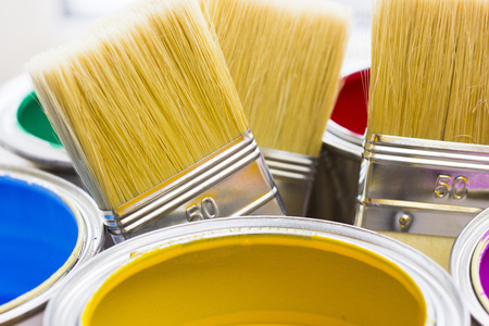 House renovation concept, colorfull paint cans and paintbrushes on wooden background top view Standard-Bild - 115543521