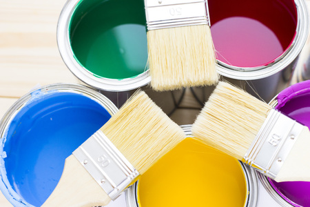 House renovation concept, colorfull paint cans and paintbrushes on wooden background top view Standard-Bild - 115543523