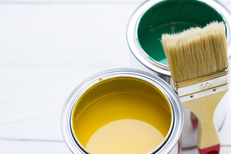 House renovation concept, colorfull paint cans and paintbrushes on wooden background top view Standard-Bild - 115543462