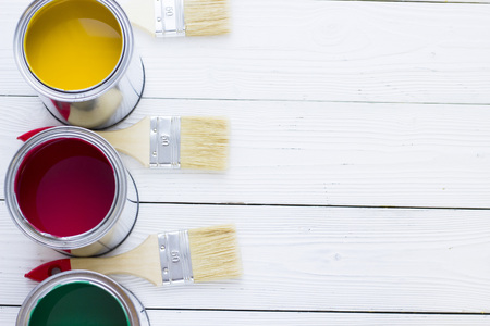 House renovation concept, colorfull paint cans and paintbrushes on wooden background top view Standard-Bild - 115543467