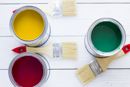 House renovation concept, colorfull paint cans and paintbrushes on wooden background top view Standard-Bild - 115543468
