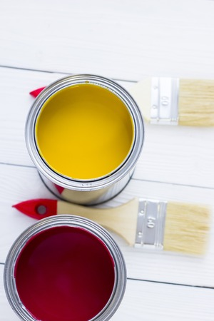 House renovation concept, colorfull paint cans and paintbrushes on wooden background top view Standard-Bild - 115543469