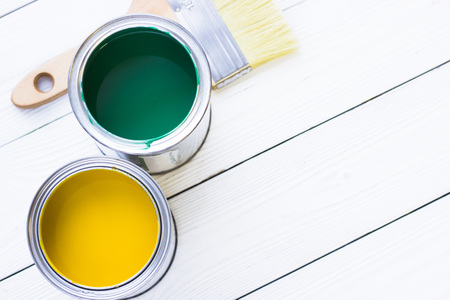 House renovation concept, colorfull paint cans and paintbrushes on wooden background top view Standard-Bild - 115543475