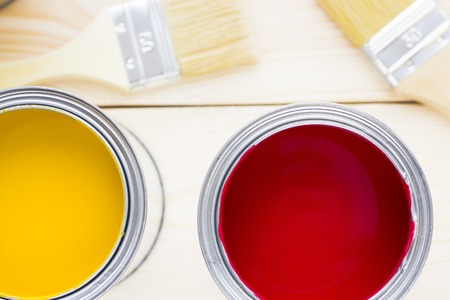 House renovation concept, colorfull paint cans and paintbrushes on wooden background top view Standard-Bild - 115543382