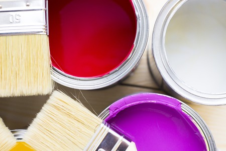 House renovation concept, colorfull paint cans and paintbrushes on wooden background top view Standard-Bild - 115543394