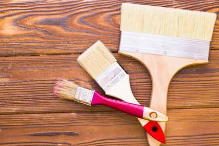 House renovation concept, colorfull paintbrushes on dark wooden background top view