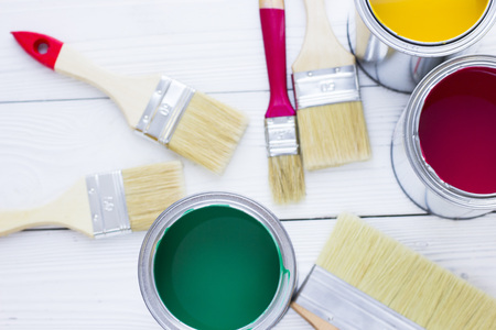 House renovation concept, colorfull paint cans and paintbrushes on wooden background top view Standard-Bild - 115543304
