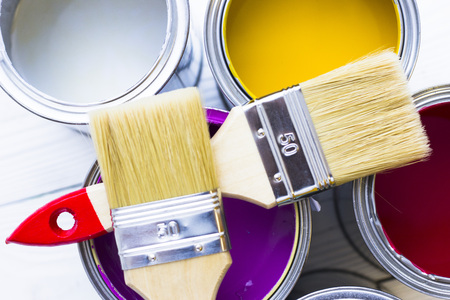 House renovation concept, colorfull paint cans and paintbrushes on wooden background top view Standard-Bild - 115543310