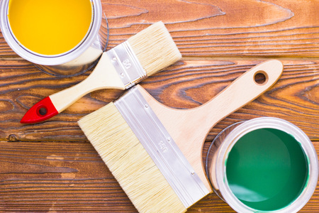 House renovation concept, colorfull paint cans and paintbrushes on dark wooden background top view Standard-Bild - 115543314