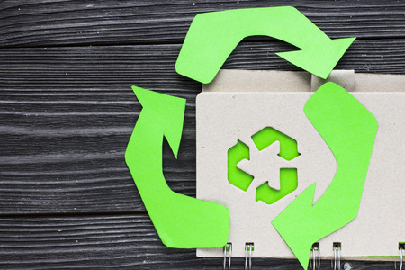 Environmental protection, ecology and recycling concept, recycle sign, notepad and garbage on dark wooden background top view closeup