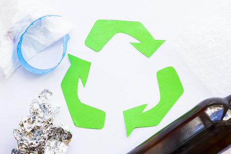 Environmental protection, ecology and recycling concept, recycle sign, notepad and garbage on white background top view closeup