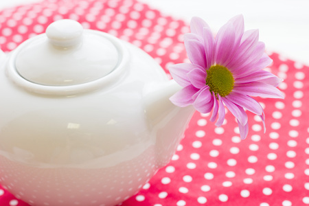 Black tea ceremony - a cup of tea, teapot, sugar, cakes, flowers on a red with white dots background, top view, closeup Archivio Fotografico - 115542932