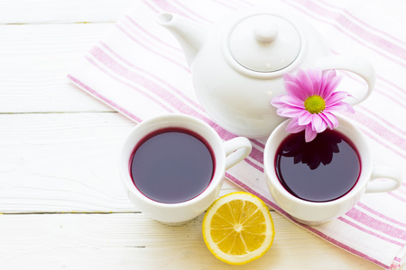 Black tea ceremony - a cup of tea, teapot, sugar, cakes, flowers on white wooden rustic background, top view, closeup