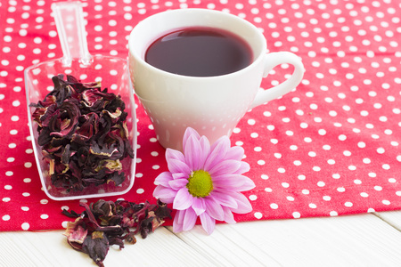Black tea ceremony - a cup of tea, teapot, sugar, cakes, flowers on a red with white dots background, top view, closeup