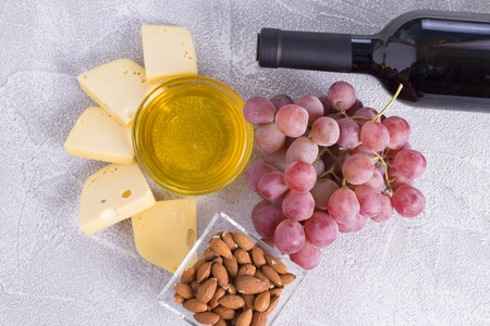 Snacks with wine - bottle, various types of cheeses, figs, nuts, honey, grapes Imagens