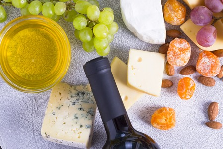 Snacks with wine - bottle, various types of cheeses, figs, nuts, honey, grapes 写真素材