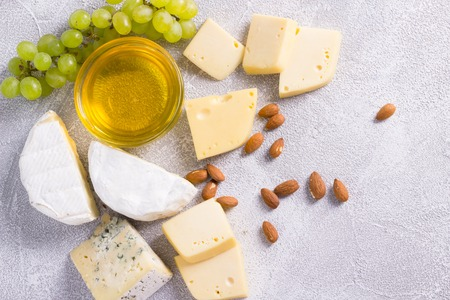 Snacks with wine - various types of cheeses, figs, nuts, honey, grapes on a white wooden background