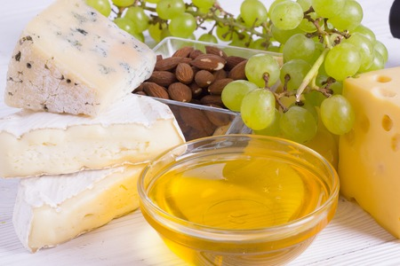 Snacks with wine - various types of cheeses, figs, nuts, honey, grapes on a white boards background