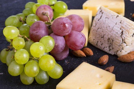 Snacks with wine - various types of cheeses, figs, nuts, honey, grapes on a black stone background 写真素材