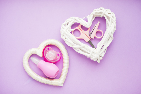 Newborn baby story. Strow heart and children's toys, scissors, baby bottle, nipple, hairbrush on violet background. Top view 스톡 콘텐츠