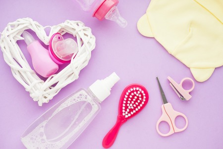 Newborn baby story. Strow heart and children's toys, scissors, baby bottle, nipple, hairbrush on violet background. Top view Foto de archivo